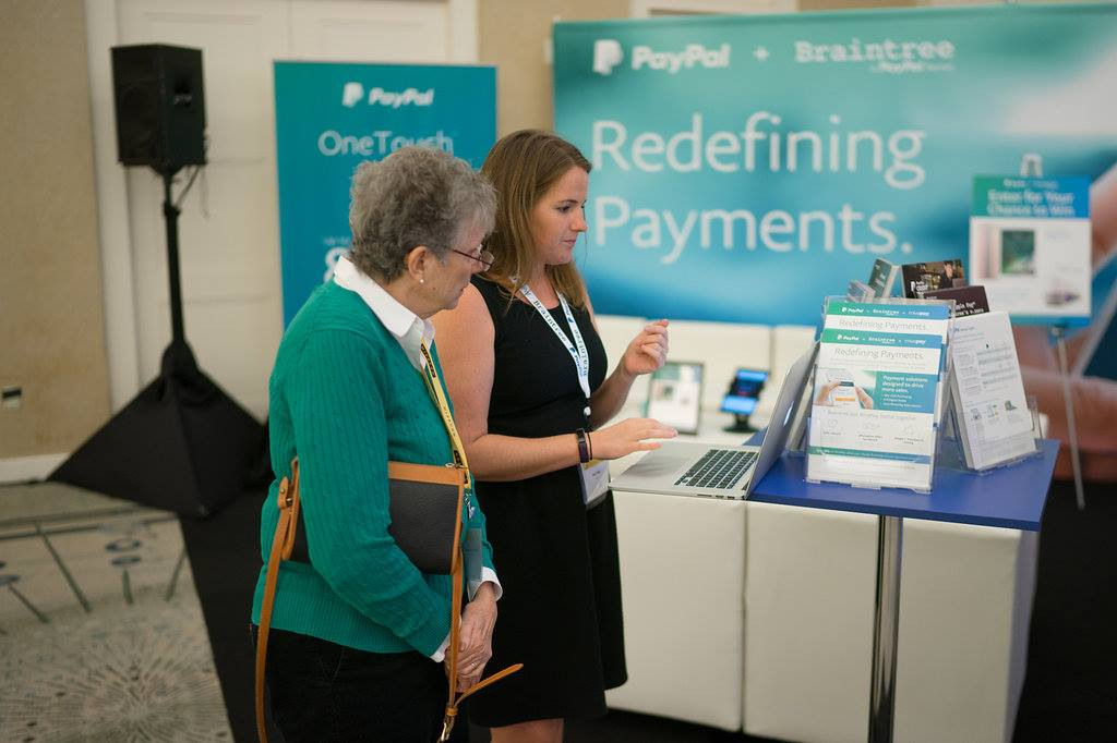 Two women talking at PayPal tradeshow booth.