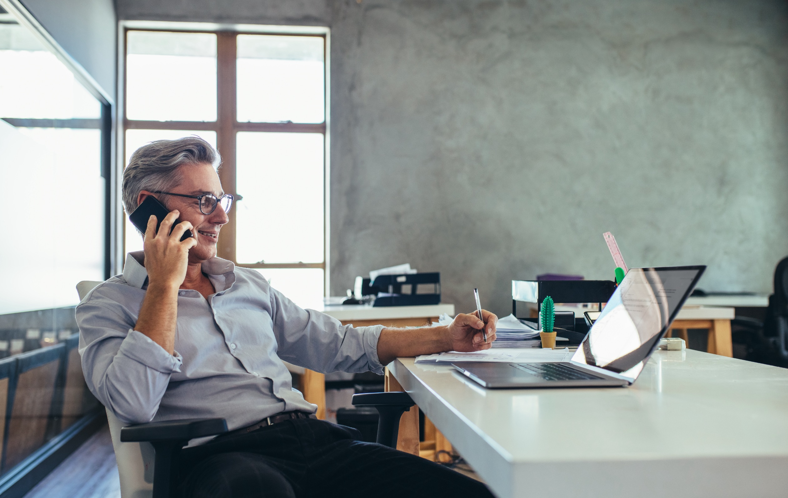 Business man sitting at a desk talking on the phone