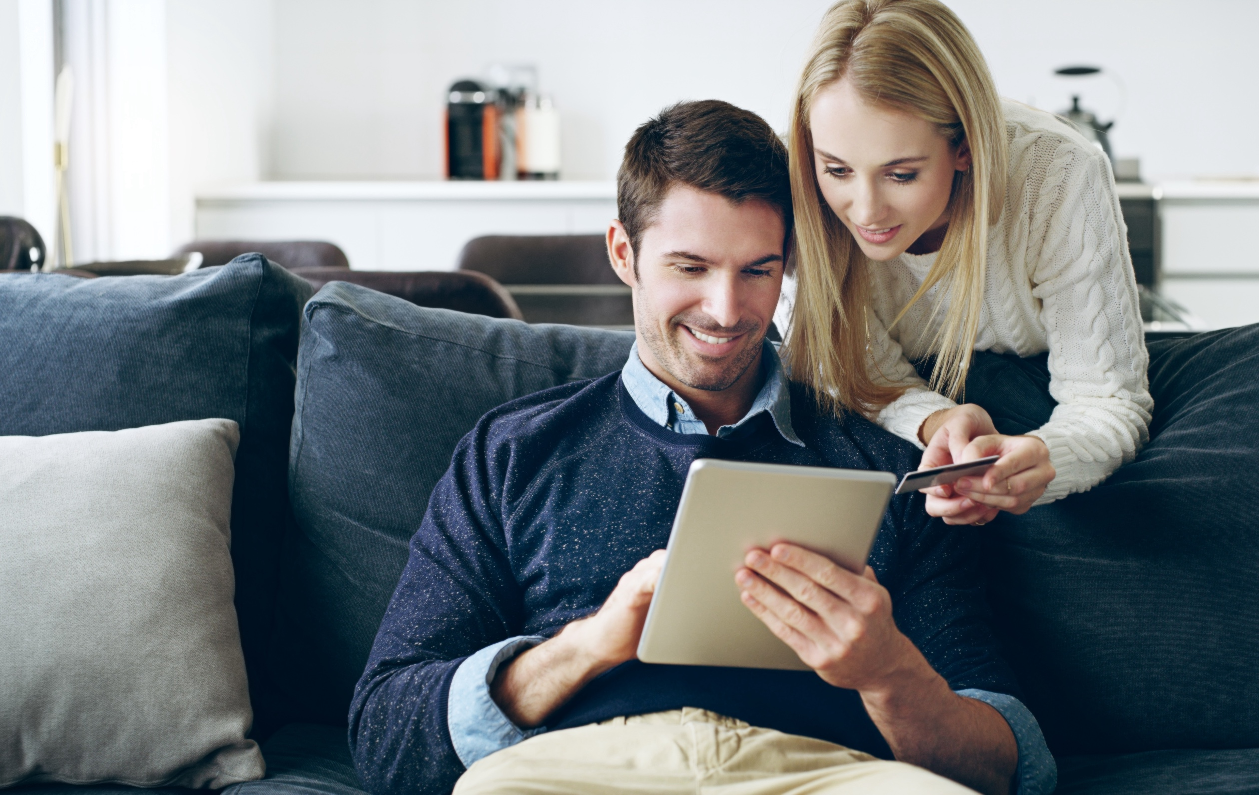 smiling couple making a purchase on a mobile device