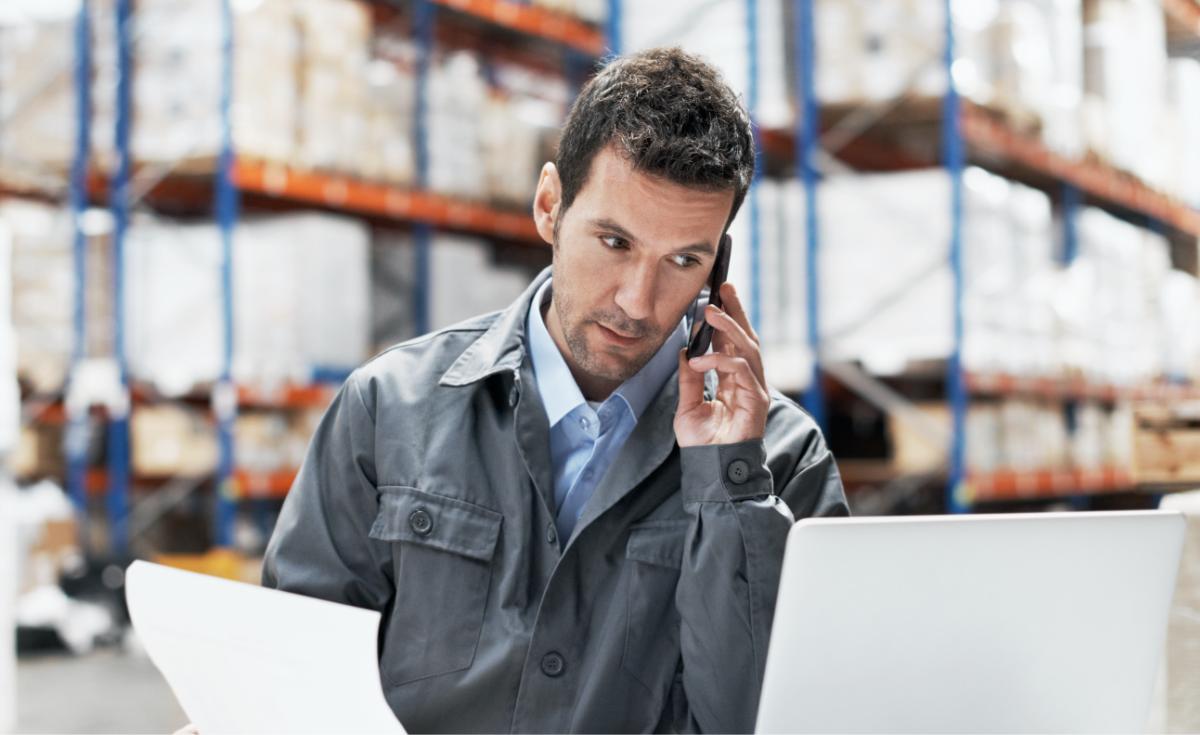 A man makes a call in a warehouse