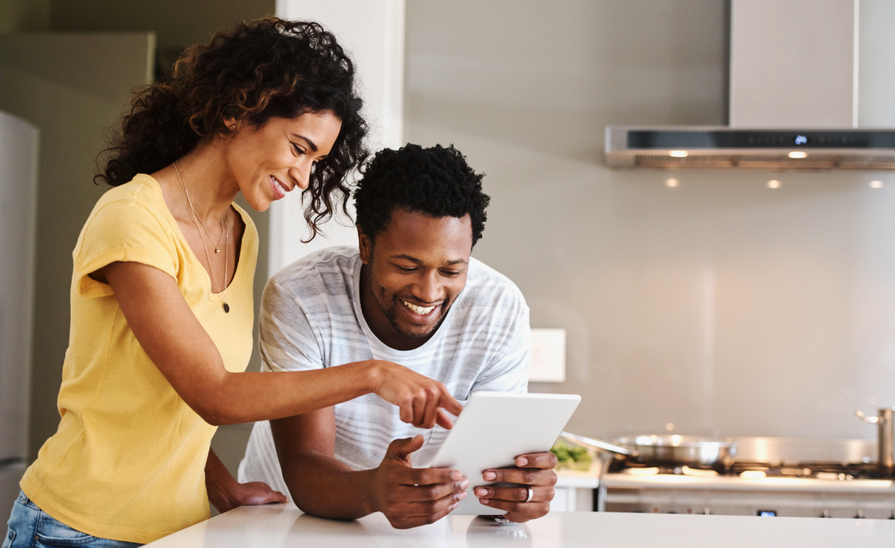 Photo of two people looking at the tablet together and smiling