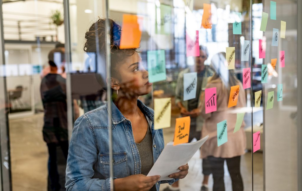 Photo of a woman looking at stiky notes on a glass wall