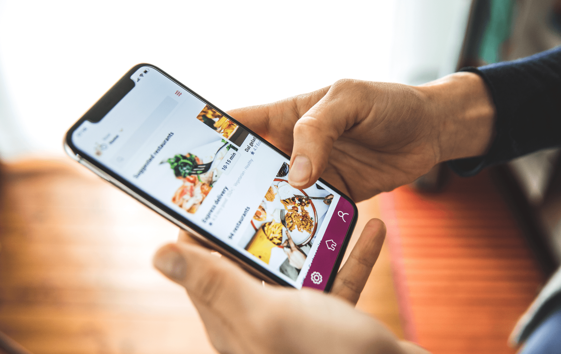 Closeup photo of the smartphone in hands. The phone screen is displaying a restaurant ecommerce website