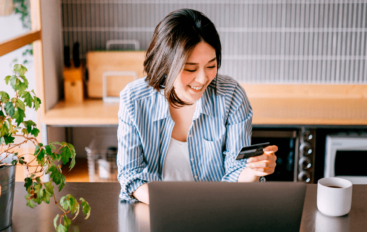 Photo of a woman sitting at the table in front of the laptop and holding a credit card while smiling