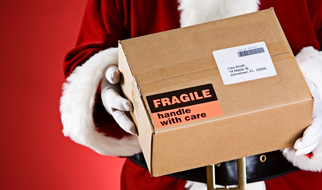 Santa Claus holding a box with fragile on the outside.